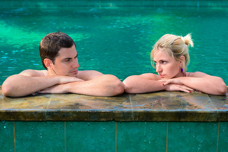 couple in pool, glaring, tension, vacation gone bad